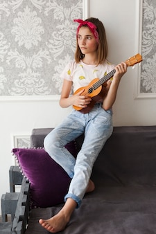 Contemplating girl holding ukulele looking away at home