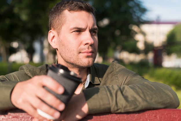 Contemplating man holding disposable coffee cup in park