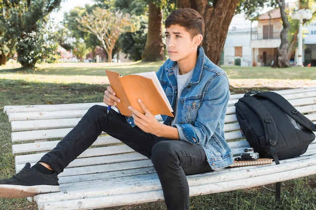 Contemplating teenage boy holding book at park
