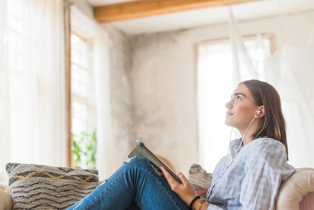 聞くことのできる音楽を持つソファに座っている女性を熟考する