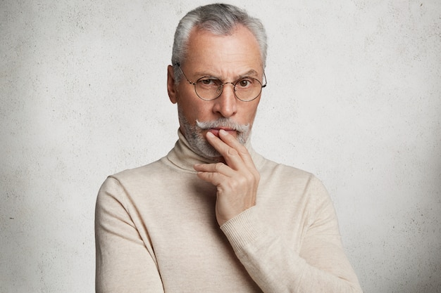 Contemplative bearded mature man in eyewear