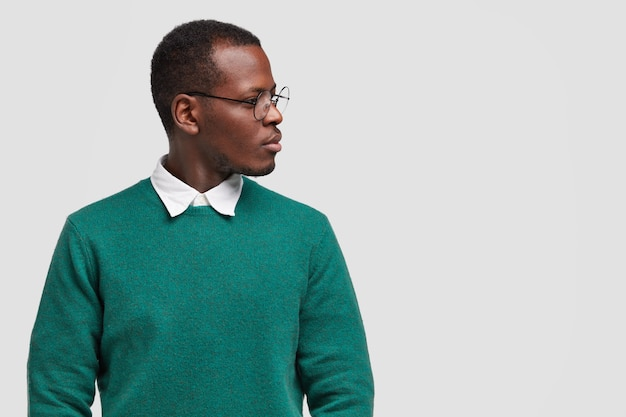 Contemplative black man focused aside with pensive expression, wears green fashionable sweater