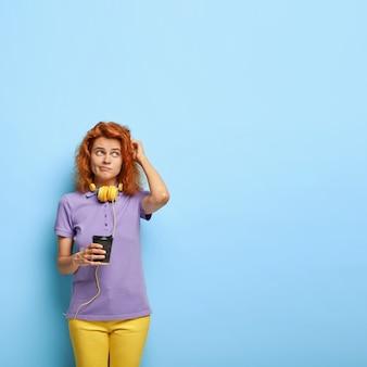 La donna dai capelli rossi confusa contemplativa graffia la testa, pensa a qualcosa