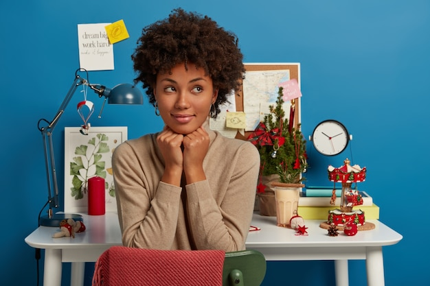 Contemplative curly woman keeps hands under chin, looks thoughtfully aside, poses against workplace decorated for christmas