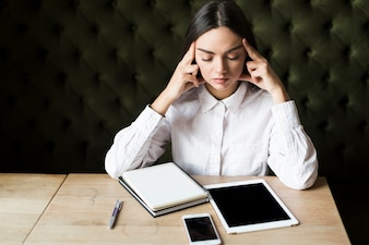 Contemplative girl with gadgets and notepad