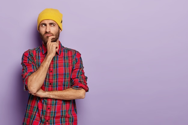 Contemplative young man holds chin, looks aside with thoughtful expression, thinks something over, wears yellow hat and plaid shirt
