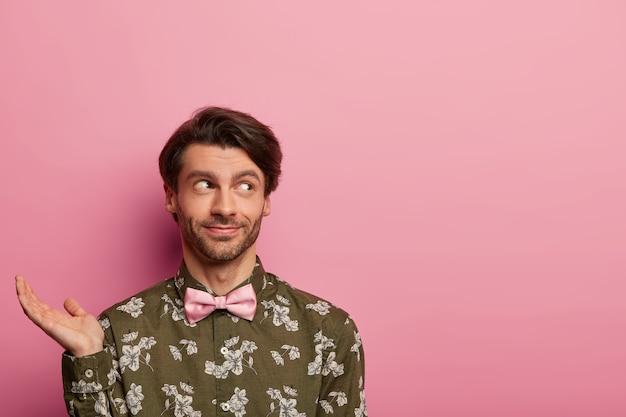Il giovane contemplativo alza il palmo, pensa a qualcosa, prende una decisione, indossa una camicia elegante con stampa floreale e papillon