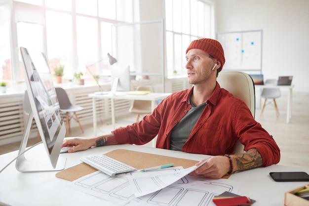 Современный взрослый человек, работающий за столом в офисе