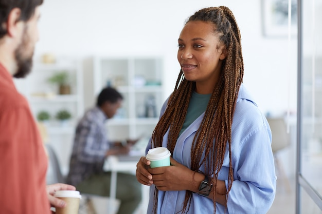 Contemporary african-american woman listening to male colleague during coffee break in office