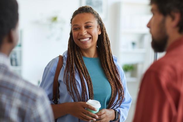 Современная афроамериканская женщина счастливо улыбается, разговаривая с друзьями или коллегами в помещении