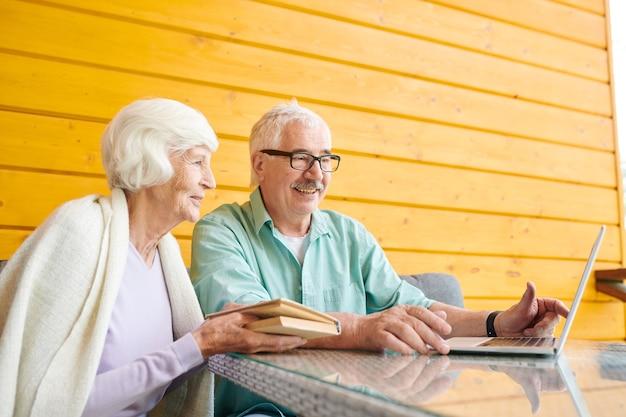 자신의 시골집에서 노트북 앞에 테이블에 앉아있는 동안 아내 온라인 정보를 설명하는 현대 세 남자