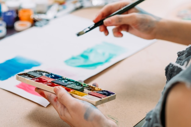 現代美術。水彩で抽象的なアートワークを作成する若い女性画家のトリミングされたショット。