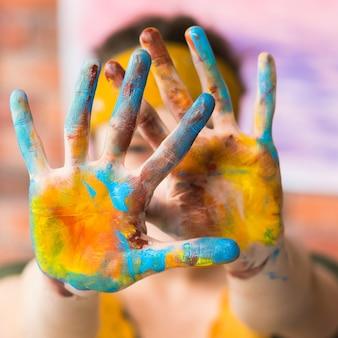 Перформанс современного искусства. крупный план женских рук грязных с красочной краской.