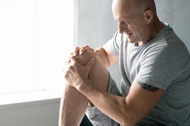 Современный лысый зрелый спортсмен в спортивной одежде массирует правое колено, сидя в физиотерапевтической клинике или медицинском кабинете