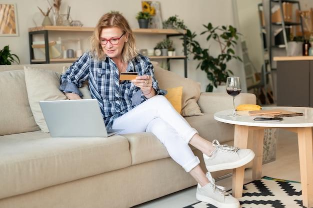 Современная блондинка зрелая женщина в белых джинсах и клетчатой рубашке сидит на диване перед ноутбуком и делает заказ в интернет-магазине