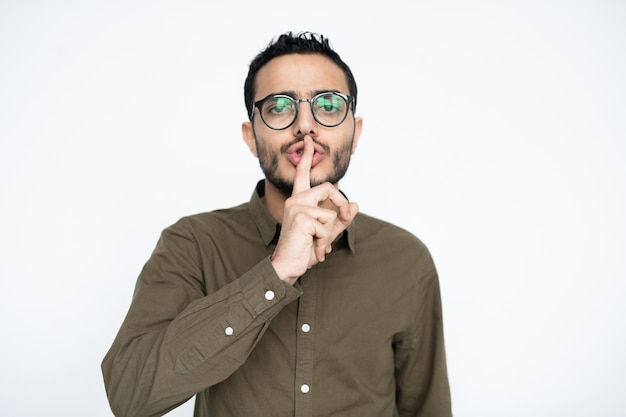 Contemporary businessman in casualwear and eyeglasses asking you to be quiet while keeping his forefinger by mouth