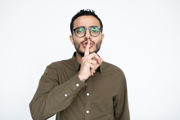 人差し指を口に入れて静かにするように求めるカジュアルウェアと眼鏡の現代的なビジネスマン