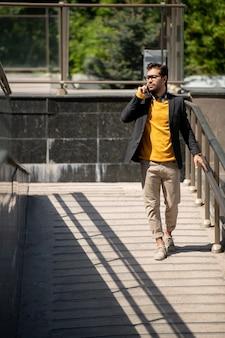 여름 날에 난간을 따라 아래로 이동하는 동안 휴대 전화로 얘기하는 현대 사업가
