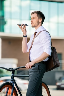 仕事の後に友人や同僚に会いに行く間、彼の口で音声メッセージを録音するスマートフォンを持つ現代のビジネスマン