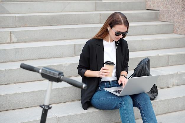 Современная повседневная девушка с бокалом кофе, смотрящая на дисплей ноутбука во время серфинга в сети на лестнице в городской среде