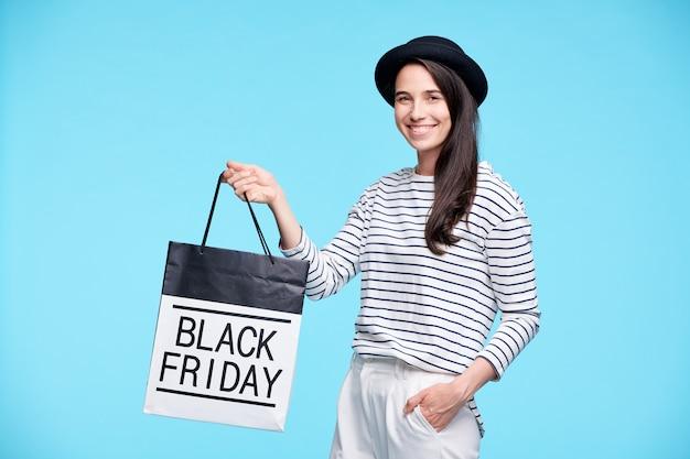 あなたを見ながら黒い金曜日の紙袋を示すスタイリッシュなカジュアルウェアの現代的な陽気な女性バイヤー