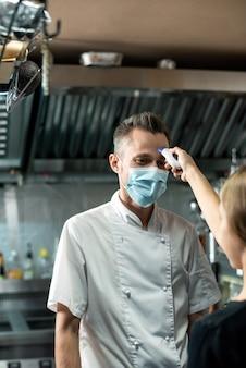 Современный повар в униформе и защитной маске смотрит на женщину с термометром, измеряющую температуру его тела перед работой на кухне