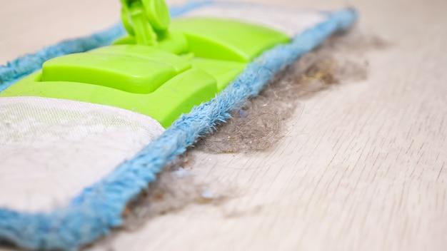 Современная красочная мягкая швабра и клочки меха, пыли и шерсти на деревянном полу в светлой комнате во время регулярной уборки. очень близко.