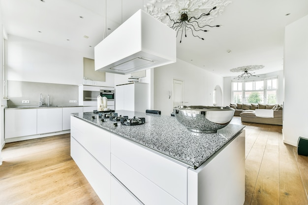 Современные столешницы и табуреты под стильной вытяжкой в просторной светлой кухне дома.
