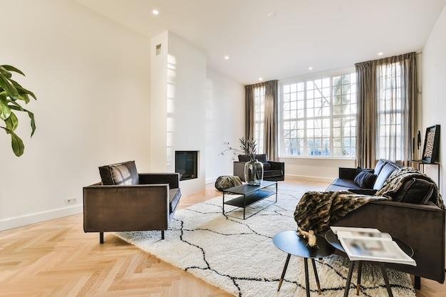 Современные уютные кресла и диван на мягком ковре в светлой современной гостиной с минималистским камином в стене
