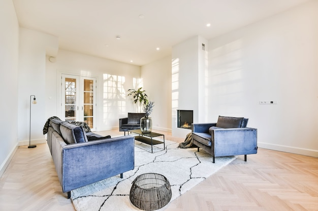 벽에 미니멀 벽난로가있는 밝은 현대 거실의 부드러운 카펫에 현대적인 아늑한 안락 의자와 소파