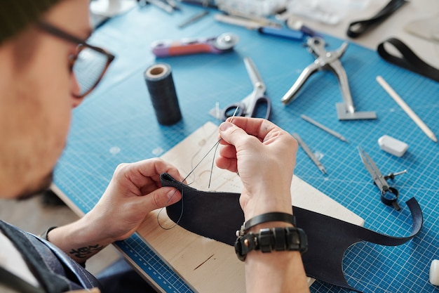 Contemporary craftsman sewing two parts of black leather together while holding them over wooden board on table