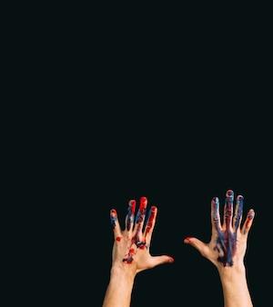 現代のクリエイティブな作品。アートクラス。才能と熟練したマスター。ペンキで汚れた男性の手。暗い背景のコピースペース。