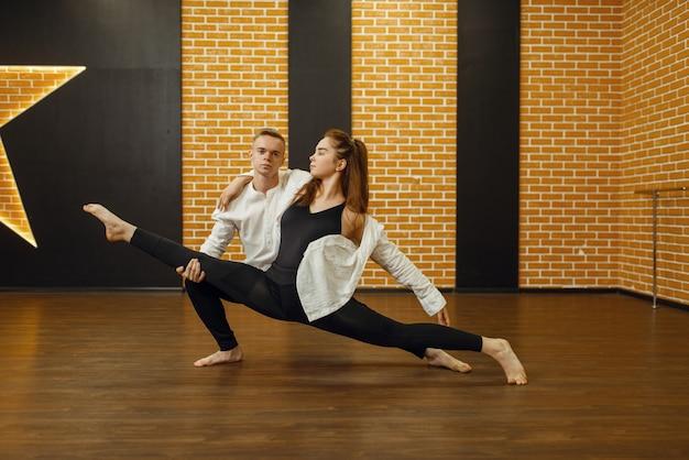 現代のダンスパフォーマー、スタジオでポーズをとるカップル。クラスでのトレーニング、モダンダンス、ストレッチ体操の男性と女性のダンサー