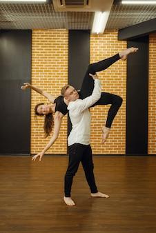 コンフォートダンスパフォーマー、スタジオでのカップルトレーニング。クラスでのトレーニング、モダンダンス、ストレッチ体操の男性と女性のダンサー