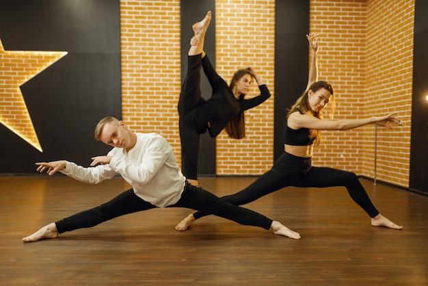 スタジオでコンテンポラリーダンスのパフォーマーがポーズをとる。クラスでトレーニングする女性と男性のダンサー、モダンな優雅なダンス、ストレッチ体操