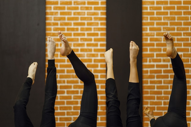 Contemporary dance performers with raised up legs in studio.