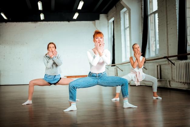 Современный танец. рыжая учительница танцев в синих джинсах и ее симпатичные ученицы приседают