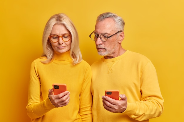 Contemporary elderly couple being confident technology users focused attentively at smartphones check information wear spectacles for vision correction isolated over yellow studio wall