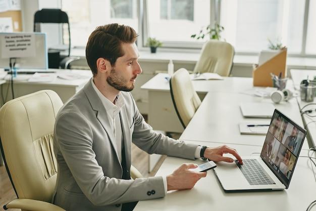 Современный элегантный бизнесмен смотрит на своих коллег, работающих из дома на дисплее ноутбука, сидя в кресле за столом в офисе