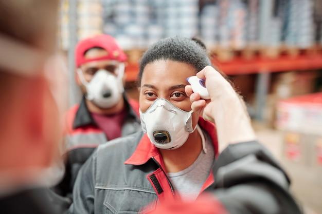 制服とレスピレーターで男性の同僚に対して彼女の温度を測定している倉庫の現代の工場労働者