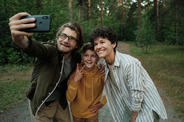 Современная семья счастливых молодых родителей и сына, стоящих рядом друг с другом в лесу или парке и делающих селфи, наслаждаясь летом