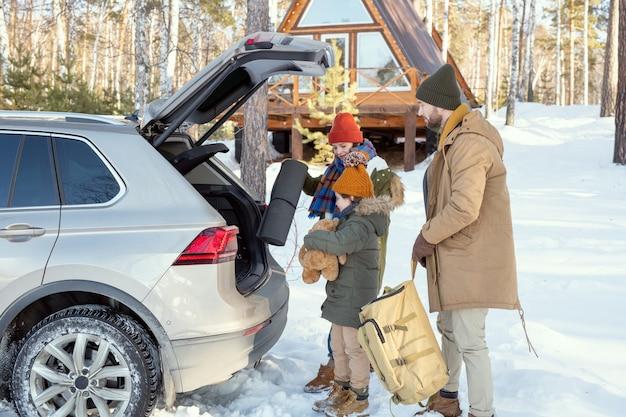 車の後ろに立って、旅行中にトランクに荷物を入れている暖かいウィンターウェアの現代的な3人家族