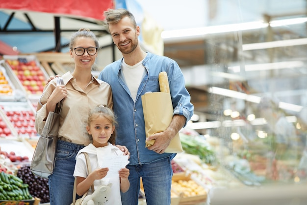 Современная семья позирует в супермаркете