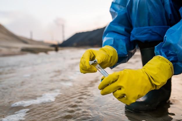 Современная женщина-эколог в резиновых перчатках и сапогах и защитных синих коналах сидит на корточках и берет образец воды