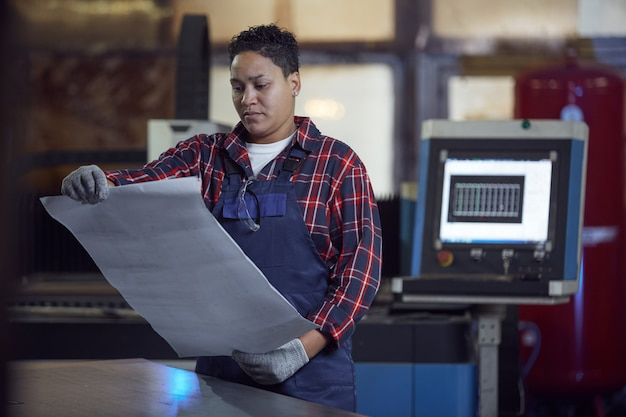 Contemporary female engineer holding plans