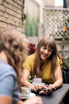 Современные подруги наслаждаются кофе за столиком в кафе, деля смартфон и улыбаясь