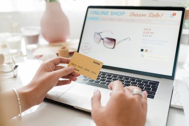 Современная женщина-покупательница держит банковскую карту над клавиатурой ноутбука, прокручивая интернет-магазин за столом