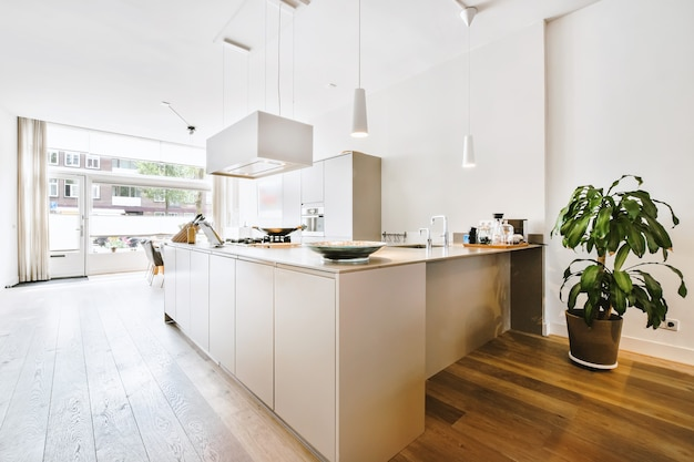 Contemporary furnished kitchen with hanging extractor hood above counter in light room with dining table
