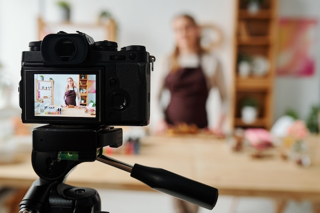 Contemporary girl on display of home camera in front of table recording soap making master class