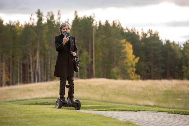 큰 녹색 잔디와 나무에 대 한 자이로 스코프에 서 있는 동안 스마트폰을 사용 하 여 검은 코트에 현대 회색 머리 사업가